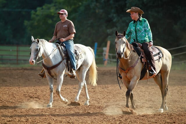 a man and woman riding their horses